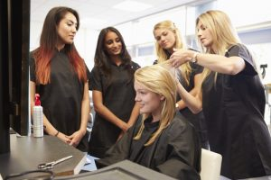 Students learn through an apprenticeship program under a professional hairdresser.